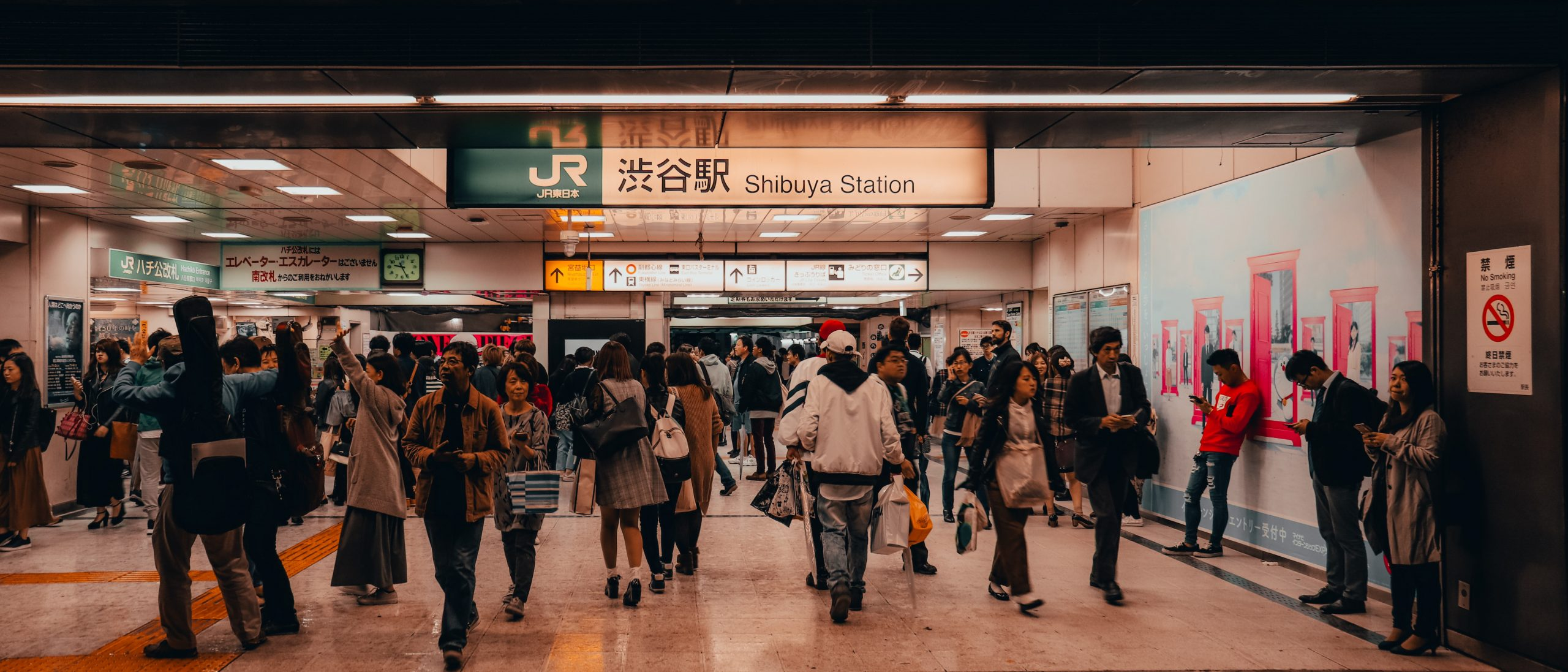 People walking through a train station in Tokyo